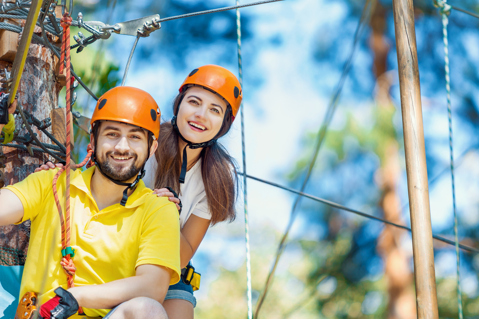 Young woman and man in protective gear are sitting on rope bridge hanging on high trees, posing and smiling. Rope adventure park with obstacles and ziplines. Extreme rest and summer activities concept